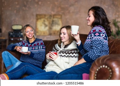 Three happy friends drinking coffee while relaxing on the sofa in the loft