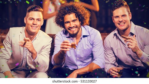 Three happy friends having cigar and whisky in bar against flying colours