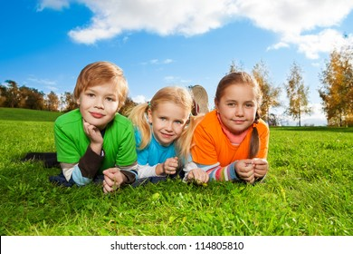 three happy friends laying on green grass in autumn park