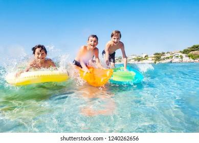 Three happy friends surfing the beach waves