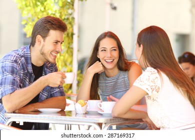 Three happy friends talking and laughing in a coffee shop terrace