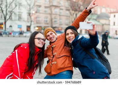 Three happy friends in a touristic city center, taking a self portrait  while visiting the city and having fun.