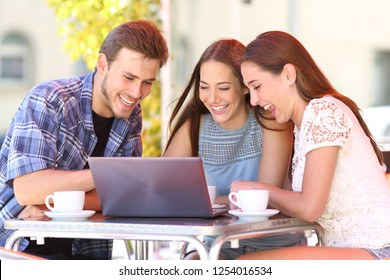 Three happy friends watching media content on a laptop sitting in a bar