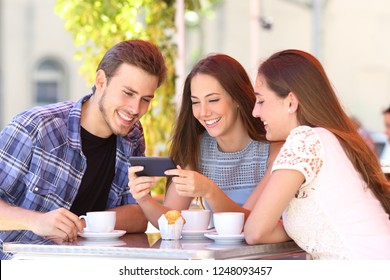 Three happy friends watching smart phone media content sitting in a coffee shop