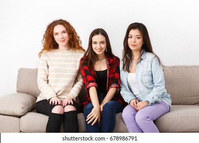 Three happy girlfriends portrait sitting on sofa at home, white background