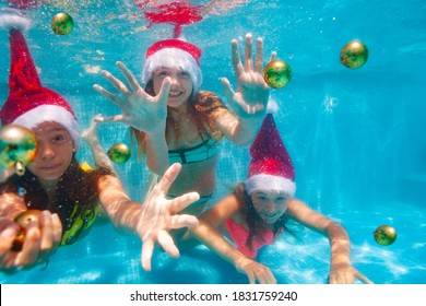 Three happy girls dive and swim underwater catching Christmas tree balls wearing Santa Claus hat in the pool