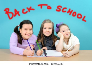 Three happy girls doing their work in classroom with back to school text