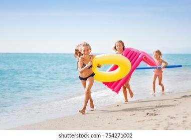 Three happy girls having fun running at the beach