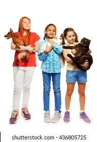 Three happy girls holding their beloved pets