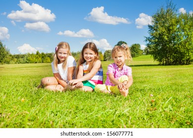 Three happy girls, sisters, sitting in the grass in park together