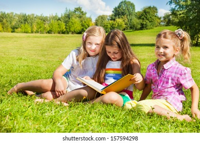 Three happy girls, sisters, sitting in the grass in park together and reading a big yellow book
