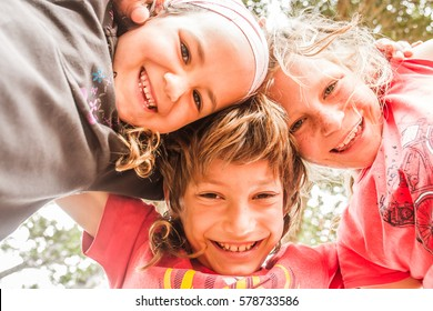 three happy kids, boy and girls, brother and sisters, on natural background looking down the camera
