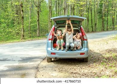 drei glückliche Kinder im Auto, Familienausflug, Sommerurlaub