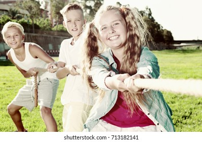Three happy kids playing active games in summer park, tugging war