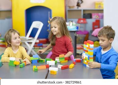 Three happy kids playing with plastic building blocks at kindergarten