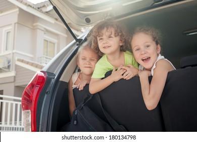 three happy kids sitting in the car