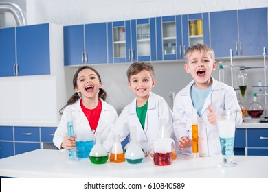 Three happy kids in white coats making chemical experiment in laboratory