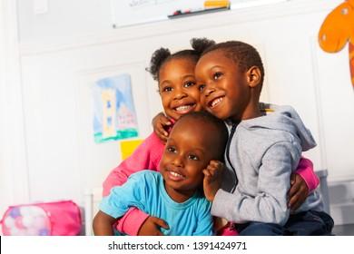 Drei glückliche kleine schwarze Kinder schließen Porträtumarmug