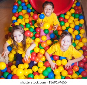 Three Happy little girls playing and having fun at kindergarten with colorful balls in play center