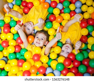 Three happy little kids girls in ball pit smiling happily at camera and show thumb up while having fun in children play center. Top view