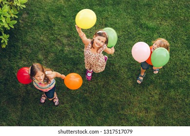 Three happy little kids playing with colorful balloons outdoors, top view