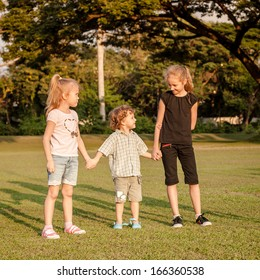 three happy little kids playing in the park in the day time