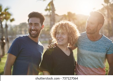 Three happy male friends standing outside looking away