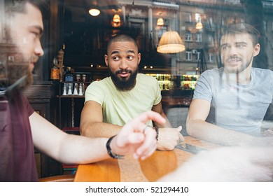 Three happy men sitting at table and speaking in restaurant