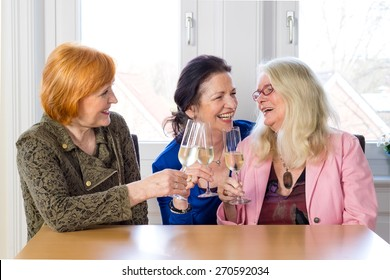 Three Happy Mom Friends Enjoying Glasses of Champagne at the Table Inside a Restaurant While Talking Funny Stories of their Lives.