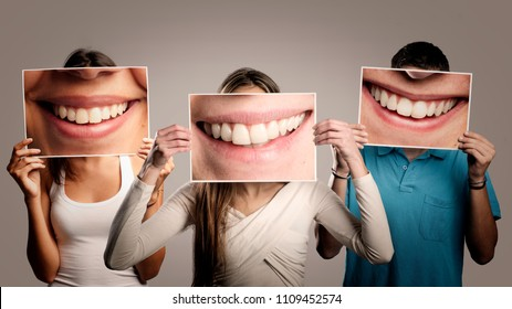three happy people holding a picture of a mouth smiling on a gray background