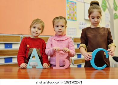 three happy preschollers girls with a b c letters in classroom