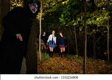 Three happy schoolgirls walking in the woods with a sinister man waiting to ambush them