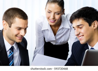 Three happy smiling businesspeople working with document at office. Teamwork, partnership, meeting, brainstorming, conculting and business success concept.