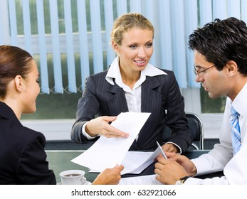 Three happy smiling businesspeople working with document at office. Success in business and teamwork concept.