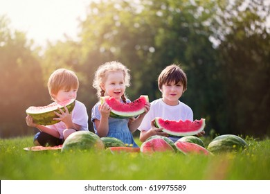 Three happy smiling child eating watermelon in park. Summer healthy food.