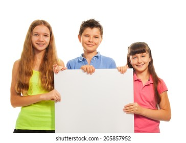 Three happy smiling friends, two girls and boy, holding blank white sign advertising
