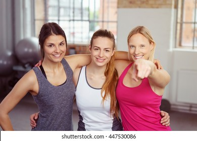 Three happy smiling girlfriends in a gym posing arm in arm with one pointing at the camera with a friendly grin