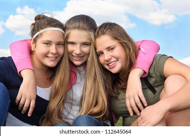 Three happy smiling girls hug at background of sky with clouds.