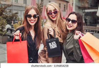 Three happy smiling girls wears sunglasses holding colorful shopping bags outdoors, black friday concept