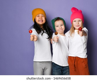 Three happy smiling joyful friends hugging kids boy and two girls in white t-shirts and colorful pants and hats hold show us sweet lollipops on blue mint background with free space