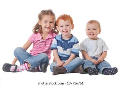 Three happy smiling kids sitting on the ground