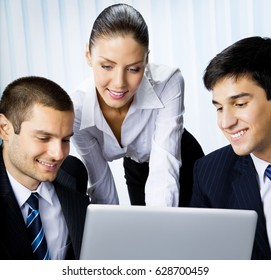 Three happy smiling successful business people working with laptop at office. Success in business and teamwork concept.
