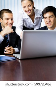 Three happy smiling successful businesspeople working with laptop at office. Teamwork, partnership, meeting, brainstorming, conculting and business success concept.