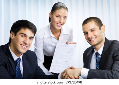 Three happy smiling successful businesspeople handshaking with document at office. Teamwork, partnership, meeting, brainstorming, conculting and business success concept.