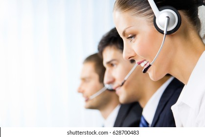 Three happy smiling young support phone operators at workplace. Call center and customer service concept.