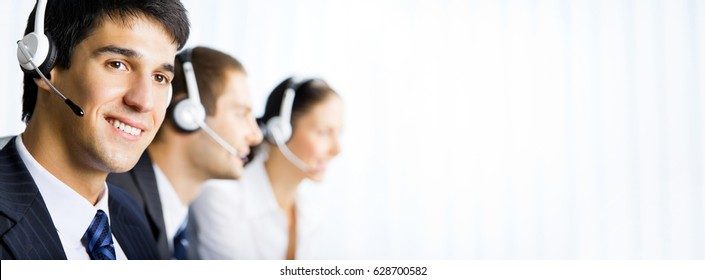 Three happy smiling young support phone operators at workplace. Blank copyspace area for slogan, advertisiment or text. Call center and customer service concept.