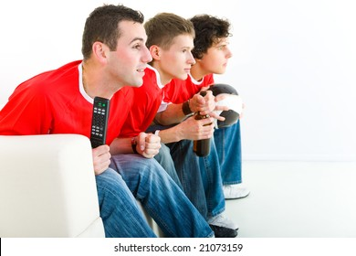 Three happy soccer fans sitting on couch and watching sport on TV. Side view.