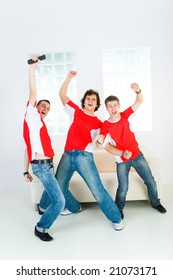 Three happy sport fans get up from couch with raised hands. Front view.