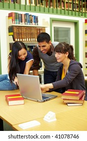 Three happy students learning in university library