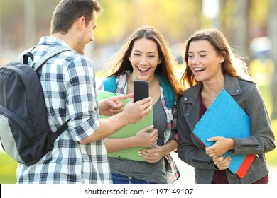 Three happy students sharing smart phone content in a park